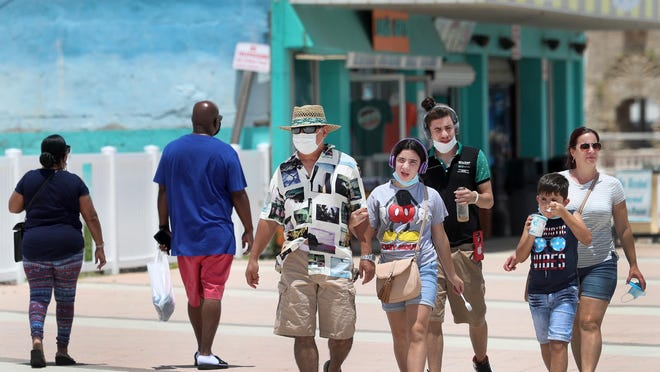 Tourists, some masked and some not, walk along the boardwalk in Daytona Beach on Friday. Even as coronavirus cases spike in Florida, visitors continue to head for the state, leaving tourism officials to strike a balance between promotion and public safety.