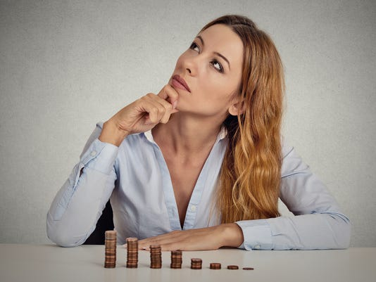 thoughtful young business woman corporate executive sitting at table with growing stack of coins