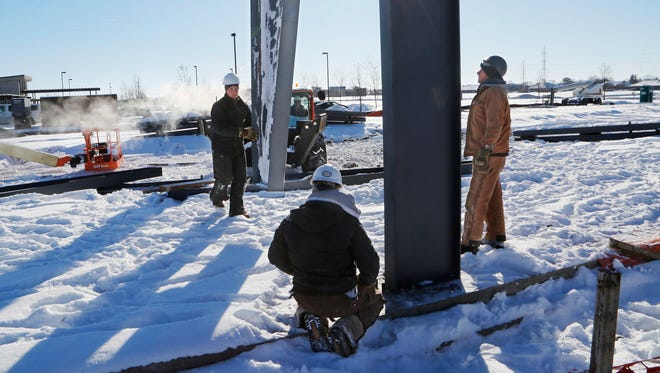 A crew from Darco Enterprises works in the frigid temperatures to erect steel for an addition to an existing building Tuesday, January 2, 2018, at 823 Park East Boulevard in Lafayette.