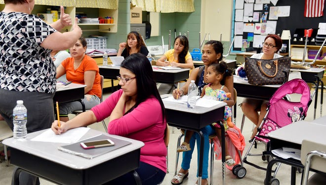 Parents, including Rosario Peña de Rodrigue, seated with her 2-year-old daughter Perla Rodrigue, listen to instructor Amy Chamberlin during an English as a Second Language class at Goode K-8 School. ESL classes are one way the district looks to connect with parents of Hispanic students, a growing population in the district.