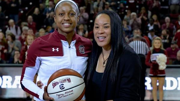 South Carolina's Tiffany Mitchell, left, is presented with a ceremonial ball by coach Dawn Staley for breaking the 1,000 career-point mark, before an NCAA college basketball game against Auburn on Friday, Jan. 2, 2015,  in Columbia, S.C. (AP Photo/Richard Shiro)