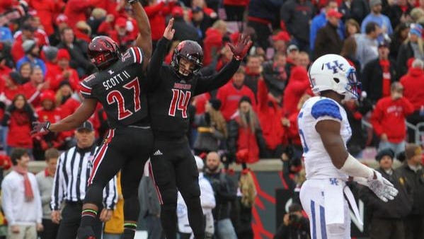 L.J. Scott and Kyle Bolin celebrate the Cardinals taking a 28-20 lead on Kentucky in the third quarter.