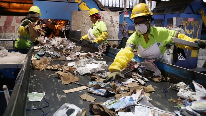 Workers at ACUA recycling center pull plastic contaminants out of the recycling stream in Egg Harbor Township, N.J.