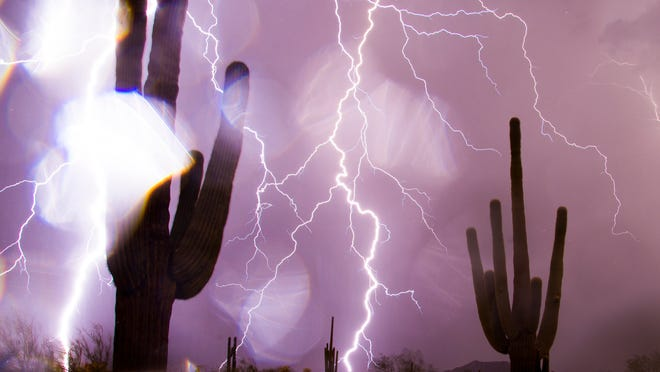 Rain drops cover the camera lens while lightning strikes over saguaros during a monsoon storm in east Mesa on July 26, 2014.
