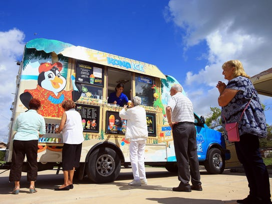Seniors gather at the Kona Ice truck to get a free
