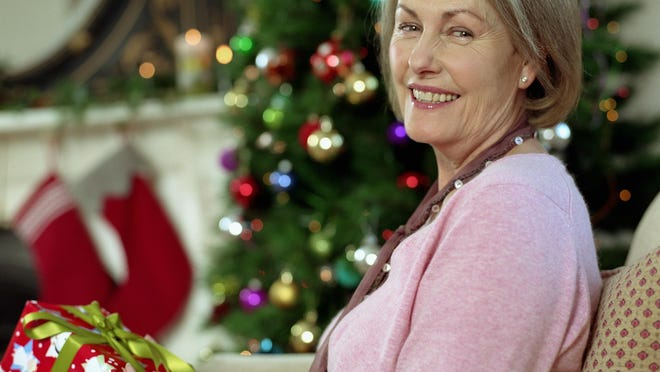 Senior woman holding a Christmas present.