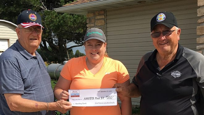 Kenny Wendt, left, finance officer for AMVETS Post 51 and Beth Wartella, Post Commander; accept a donation check from Tom Schmelzer, owner of 27 Pines and member of the Door County Tavern League.