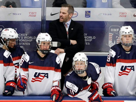 FILE - In this April 3, 2017, file photo, United States head coach Robb Stauber, rear center, shouts in the bench area during the third period of a IIHF Women's World Championship hockey tournament game against Finland in Plymouth, Mich. Even though Stauber has coached Americans in the Winter Games before, Pyeongchang will mark his debut as head coach on the biggest stage for women's hockey. (AP Photo/Carlos Osorio, File)