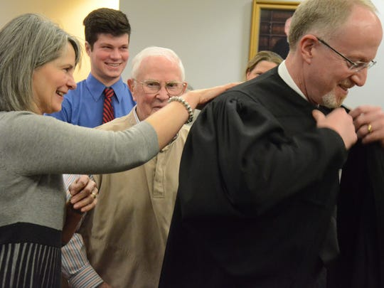 Circuit Judge John Hallacy is helped with his robe
