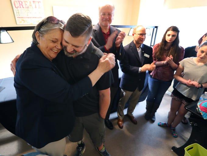 Catherine W. Cook, embraces US Army SSG Daniel Burgess