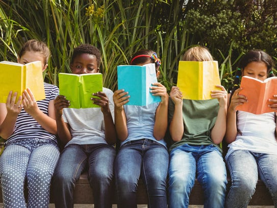 Children read books while sitting on a park bench.