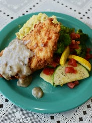 The fried chicken with gravy, mashed potatoes and vegetables