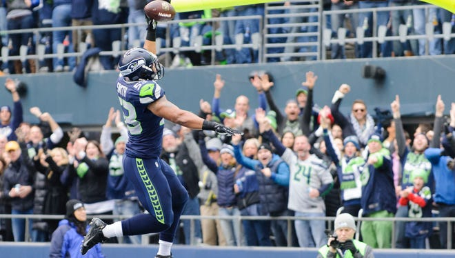 Seahawks LB Malcolm Smith dunks the ball after his pick six Sunday.