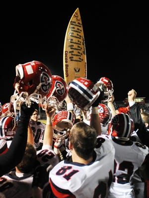 Cocoa Beach players celebrate keeping the Beach Bowl trophy surfboard in 2012.
