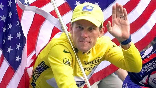 Lance Armstrong rides down the Champs Elysees with an American flag after winning the Tour de France in 2000.
