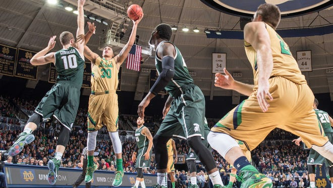 Dec 3, 2014; South Bend, IN, USA; Notre Dame Fighting Irish forward Austin Burgett (20) goes up for a shot a Michigan State Spartans forward Matt Costello (10) defends in the first half at the Purcell Pavilion. Mandatory Credit: Matt Cashore-USA TODAY Sports