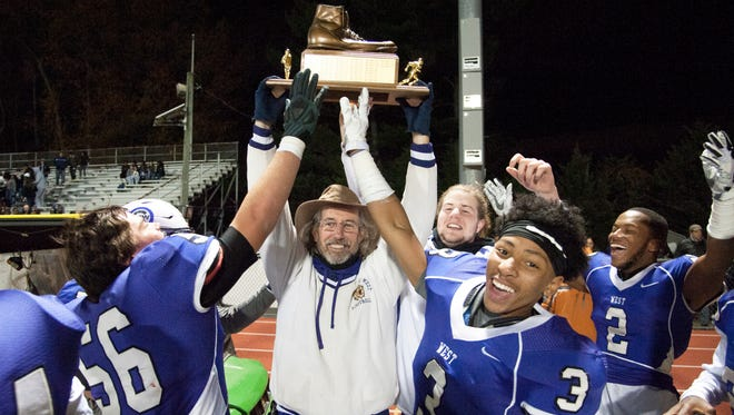Cherry Hill West's athletic trainer John Laird, center, celebrates with memers of the Cherry Hill West football team, as Laird hoists the Al DiBart Memorial Trophy after Cherry Hill West beat Cherry Hill East, 48-12, in Wednesday night's Thanksgiving Eve football game played at Cherry Hill West. Laird, who will be retiring in January 2018, was honored during the game for his 30 year career at Cherry Hill West.  11.22.17