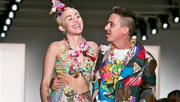 Entertainer Miley Cyrus, left, joins fashion designer Jeremy Scott for a walk on the runway after he showed his Spring 2015 collection during Fashion Week on Wednesday in New York.