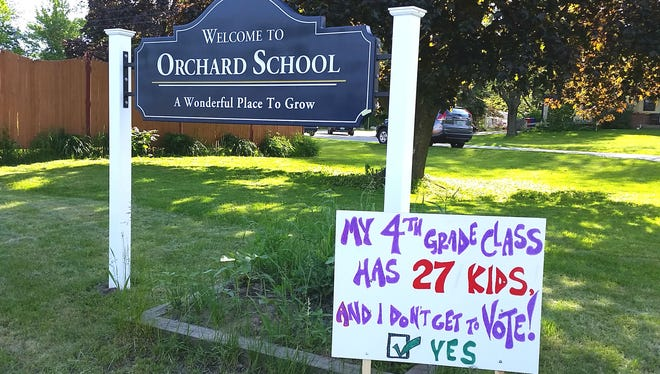 A handmade sign planted by the entrance to Orchard School in South Burlington on June 2, 2017m urges passage of the school budget on behalf of 4th graders at the school.