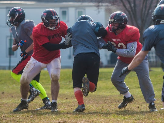 Greg Day, right, and a teammate help block a player on March 6, 2016 during practice in Hanover.