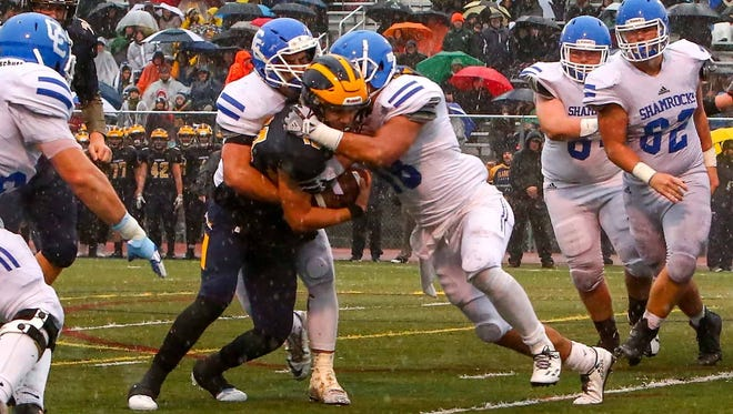 Catholic Central's Matt Young (48) helps bring down Clarkston's Nate Uballe.