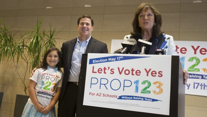 Sharon Harper, chairwoman of Greater Phoenix Leadership, speaks about Proposition 123 passing as Gov. Doug Ducey listens with Finn Wallace at Camelback Tower on Thursday, May 19, 2016 in Phoenix.
