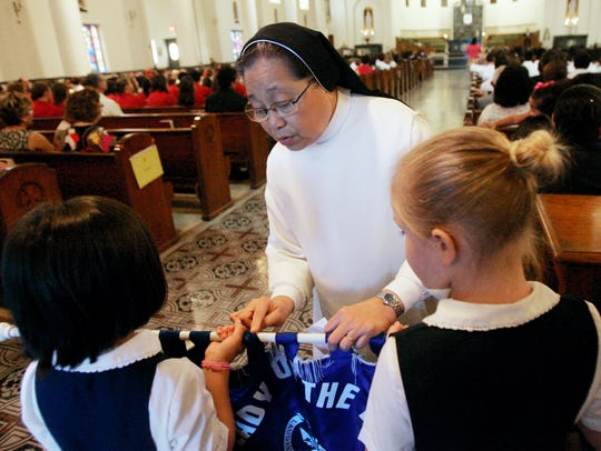 Sister Paz Aribon helps students from Our Lady of the
