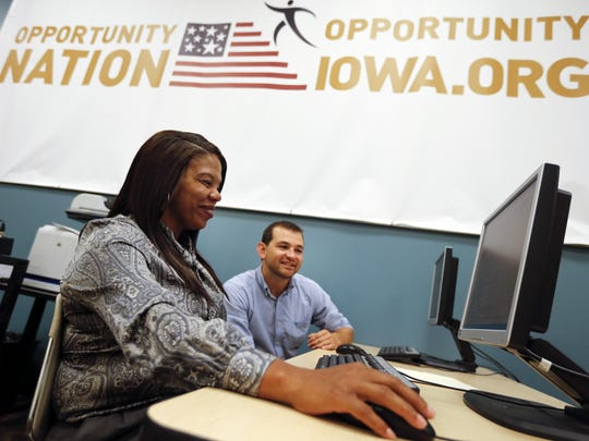 Roshanda Rushing looks for jobs online with help from Zach Steele, training coordinator at the Evelyn K. Davis Center Monday, Aug. 24, 2015.