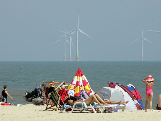 People sunbathe on the beach in front of turbines,