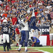 Arizona Cardinals free safety Rashad Johnson (26) reacts as St. Louis Rams offensive tackle Rob Havenstein (79) hoists Tavon Austin into the air following his touchdown Oct. 4 in Glendale, Ariz.