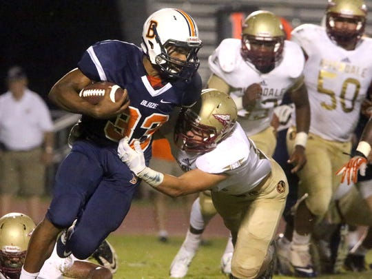 Blackman's Master Teague (33) runs the ball as Teague is tackled by Riverdale's Austin Valentine (28) at the game at Blackman, on Friday Sept. 4, 2015.