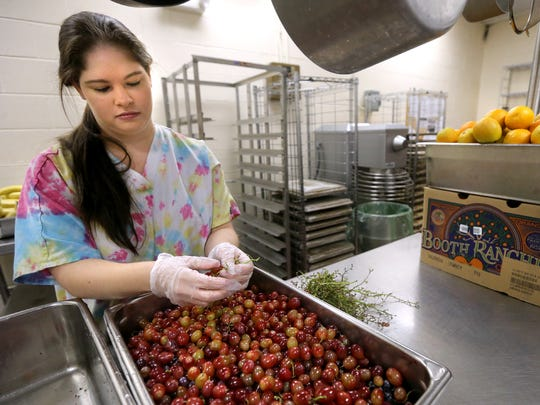 Ashley Kemp with the cafeteria staff at Christiana Elementary School prepares grapes for lunch at the school on Wednesday Oct 28, 2015.