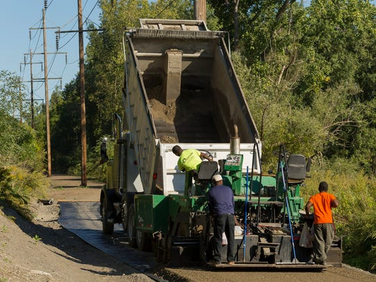 A crew working for CC Paving and Excavating, of Syracuse, lays down gravel for the subbase on top of a waterproof barrier fabric Wednesday morning for the Black Diamond Trail near the trail's southern end at Cass Park. The finished trail surface will be a fine stone dust, forming a hard surface.