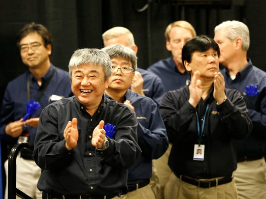 President and CEO Eiji Ogino, foreground left, applauds