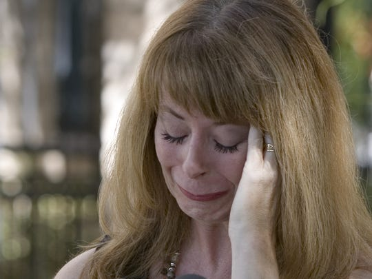 An emotional Wendy Carr, Mark Goudeau's wife, reads a statement during a press conference in September 2006 outside her attorney's Phoenix office.