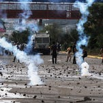 Tear gas flies during clashes between police and protesters near the National Autonomous University in Tegucigalpa, Honduras, Tuesday, Nov. 26, 2013.