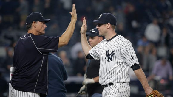 New York Yankees third baseman Chase Headley, right, high-fives hitting coach Alan Cockrell after the Yankees defeated the Kansas City Royals 7-3 in a baseball game Thursday, May 12, 2016, in, New York.