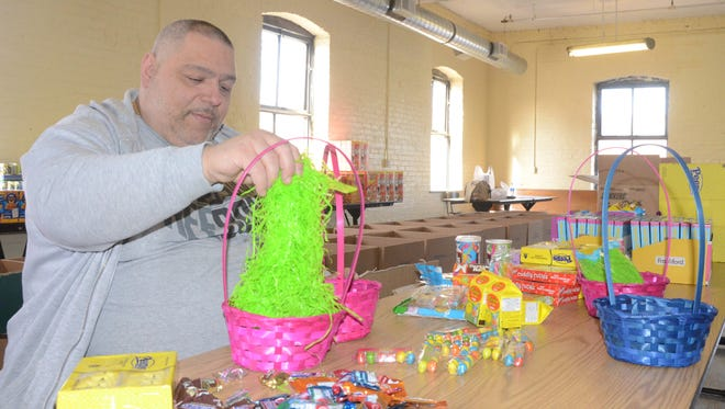 Alphonse Bifulco adds the grass to an Easter basket Friday afternoon preparing for a food and candy distribution.
