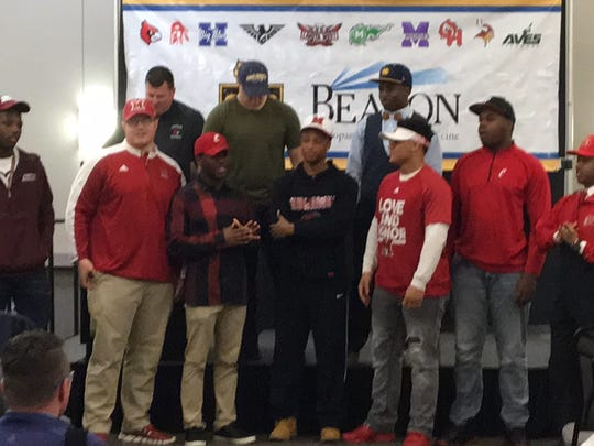 Colerain head football coach at the podium with senior signees. Front row, from left, Jakari Patterson (Southern Illinois), Rusty Feth (Miami), JJ Davis (UC), Syncere Jones (Miami), Ivan Pace (Miami), Eric Phillips (UC), Alonzo Kendricks (Indiana Wesleyan). Back row: Cutright, TJ Gonella (Siena Heights), Deante Smith-Moore (Mississippi College), at the Greater Miami Conference football signing celebration, Feb. 6, 2019, Sharonville Convention Center.
