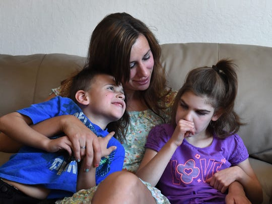 Karessa Battenfeld sits between her son Austin, left, and daughter Autumn