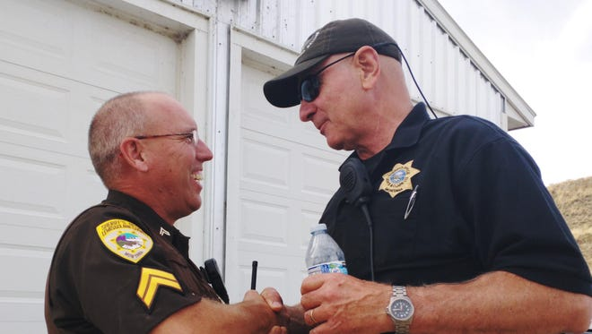 """Deputy Steve Adsem, left, and John McKittrick, right, shake hands and congratulate each other on apprehending Branden Miesmer. """"He's on his way to jail so everybody's smiling right now,"""" McKittrick said."""