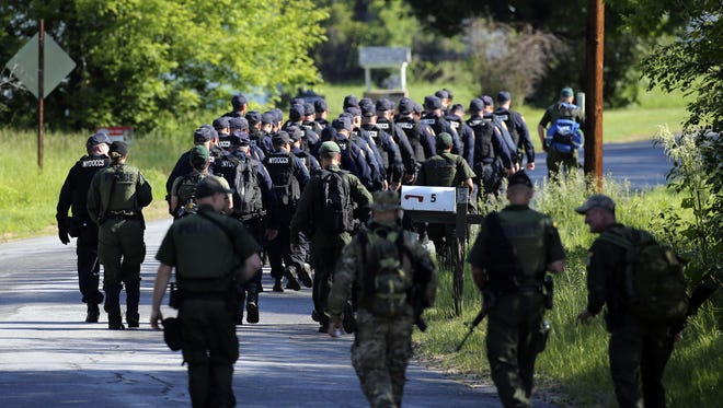 Law enforcement officers walk along Delisle Road on Saturday, June 13, in Saranac, N.Y. Hundreds of law enforcement personnel have begun an eighth day searching for David Sweat and Richard Matt, two killers who used power tools to cut their way out of Clinton Correctional Facility in Dannemora in northern New York.