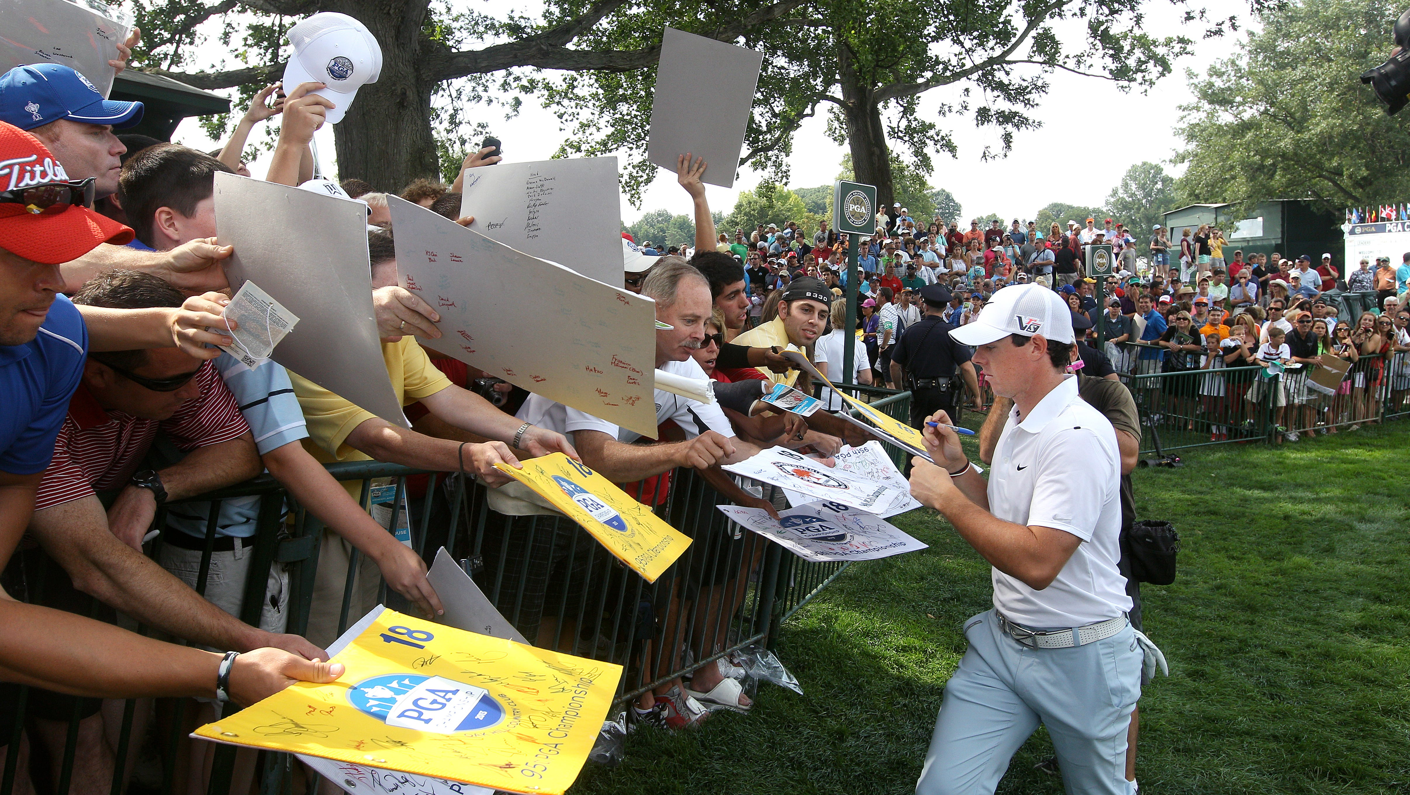 Defending PGA champion Rory McIlroy signs autographs for fans after finishing the 18th hole during a practice round.