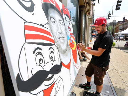 Matthew Dayler, works on a Reds Todd Frazier painting during Second Sunday on Main in Over-the-Rhine. Dayler is the founder and lead artist of Higher Level Art. The painting was part of a Reds/MLB pop-up gallery on Main by Corporate, a sneaker store in Hyde Park. The painting is an Art on the Street project aimed to bring awareness to crosswalks. The gallery is up through Tuesday.