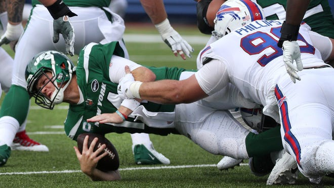 Jet quarterback Sam Darnold is tackled by Bills Harrison Phillips.
