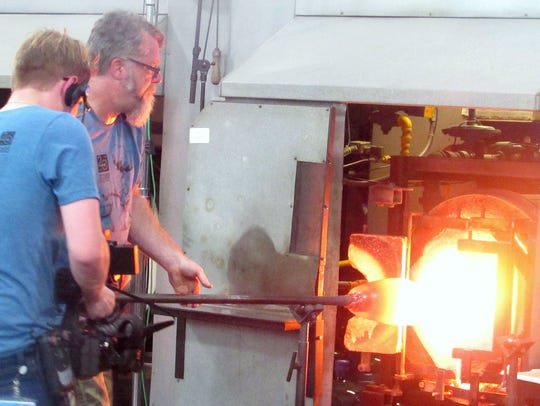 Glass artist John Miller pulls a hunk of molten glass