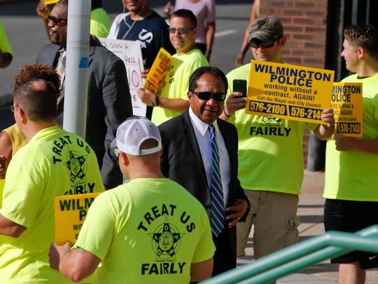 Wilmington Mayor Dennis P. Williams walks past protesting police officers to a mayoral debate.