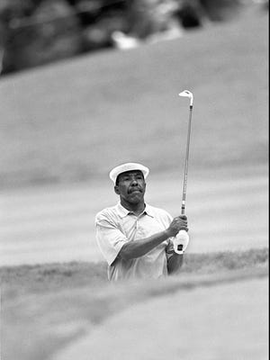 In a file photo from 1995, Calvin Peete watches his bunker shot on 15 in opening round of the U.S. Senior Open in Bethesda, Md.