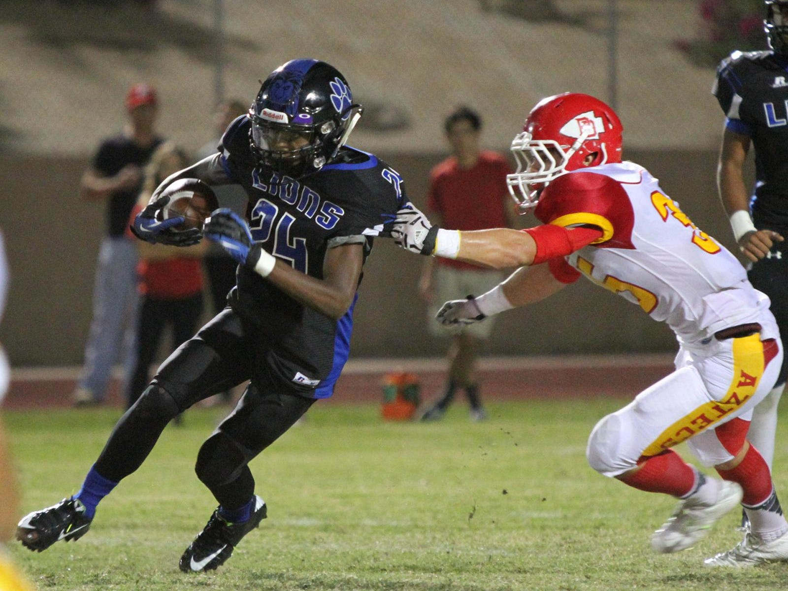10/16/15 Taya Gray, Special to The Desert Sun Cathedral City's James Green III runs the ball as Palm Desert's Denton Anderson gets a grab of his jersey during the first half of the game in Cathedral City on Friday, October 16, 2015.