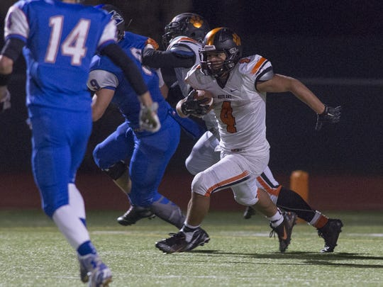 Woodlake's Noe Garcia (4) runs for extra yards during Friday's Central Section Division V semifinal game in 2015.